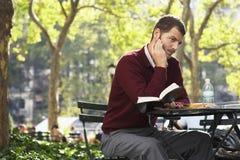 Uomo d'affari Holding Book And Pen In Park Fotografia Stock