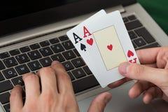 Uomo d'affari Holding Cards While che per mezzo del computer portatile Fotografie Stock Libere da Diritti