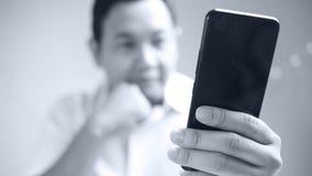 Uomo d'affari Holding e Smart Phone usando immagine stock libera da diritti