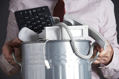Uomo d'affari Holding Garbage Can con i mobili d'ufficio obsoleti Fotografia Stock Libera da Diritti