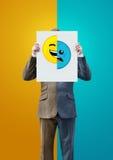 Uomo d'affari Holding Happy e fronti tristi Fotografia Stock