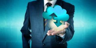 Uomo d'affari Holding un'icona solida di trasferimento della nuvola immagine stock