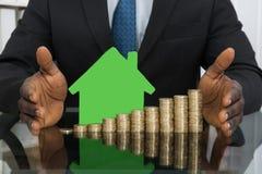 Uomo d'affari With House Model e monete Immagine Stock