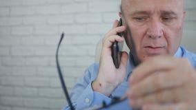 Uomo d'affari Image Talking al cellulare e giocare con gli occhiali fotografia stock libera da diritti