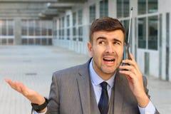 Uomo d'affari imbarazzato che per mezzo del telefono senza fili obsoleto con l'antenna immagine stock
