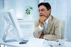 Uomo d'affari indeciso al suo computer Immagini Stock