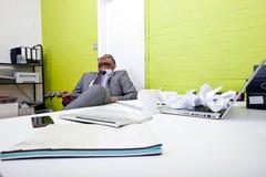 Uomo d'affari indiano addormentato al suo scrittorio che innesta ukulele Fotografie Stock