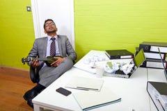 Uomo d'affari indiano addormentato al suo scrittorio che innesta ukulele Immagine Stock