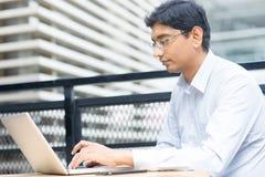Uomo d'affari indiano facendo uso del computer portatile Fotografia Stock