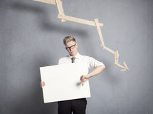 Uomo d'affari infelice che mostra comitato davanti al grafico discendente. Immagine Stock Libera da Diritti