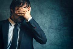 Uomo d'affari infelice nell'ambito dello sforzo dopo guasto di progetto di affari Fotografia Stock