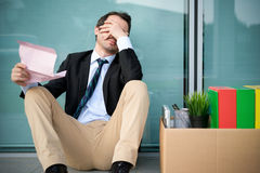 Uomo d'affari infornato che legge l'avviso del termine di lavoro fotografia stock libera da diritti