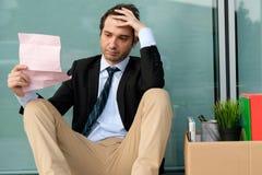 Uomo d'affari infornato che legge l'avviso del termine di lavoro fuori fotografie stock