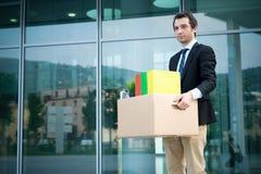 Uomo d'affari infornato che porta via i suoi effetti personali in Wall Street Immagini Stock