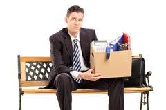 Uomo d'affari infornato che tiene una scatola con la sua roba fotografia stock libera da diritti