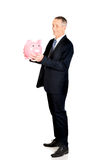 Uomo d'affari integrale di vista laterale con il porcellino salvadanaio Fotografie Stock
