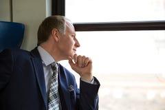Uomo d'affari interessato a cui vede attraverso a finestra Fotografie Stock