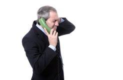 Uomo d'affari interessato sul telefono Immagini Stock