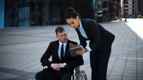 Uomo d'affari invalido del capo in sedia a rotelle il suo lavoro di segretario di signora con il cuscinetto di Digital stock footage
