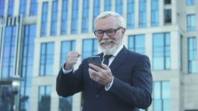 Uomo d'affari invecchiato felice che riceve buone notizie, facenti sì-gesto, app per l'affare video d archivio