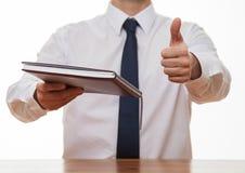 Uomo d'affari irriconoscibile che dà un libro e che mostra un pollice su Immagine Stock Libera da Diritti