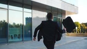 Uomo d'affari irriconoscibile con i funzionamenti della cartella giù la via della città Uomo di affari recente per incontrarsi Ri stock footage