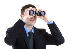 Uomo d'affari isolato sullo sguardo bianco tramite il binocolo Fotografia Stock Libera da Diritti