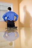 Uomo d'affari ispanico che osserva fuori la finestra dell'ufficio Fotografia Stock Libera da Diritti