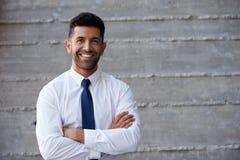 Uomo d'affari ispano Standing Against Wall in ufficio moderno Fotografia Stock Libera da Diritti