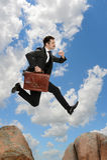 Uomo d'affari Jumping From Rock Immagine Stock Libera da Diritti