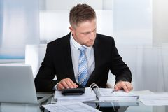 Uomo d'affari laborioso che analizza un rapporto Fotografie Stock Libere da Diritti