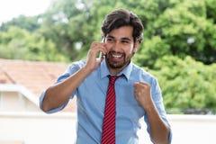 Uomo d'affari latino incoraggiante con la barba al telefono cellulare Fotografie Stock Libere da Diritti