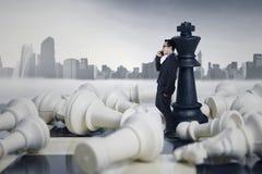 Uomo d'affari Leaning alle figure di scacchi Fotografie Stock