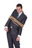 Uomo d'affari legato su nella corda Immagine Stock