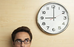 Uomo d'affari Looking At Clock sulla parete di legno in ufficio Fotografia Stock Libera da Diritti