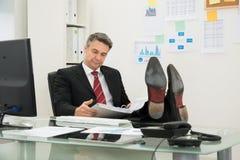 Uomo d'affari Looking At Folder fotografie stock
