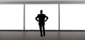 Uomo d'affari Looking Out una grande finestra Immagine Stock Libera da Diritti