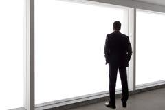 Uomo d'affari Looking Out una grande finestra Fotografia Stock Libera da Diritti
