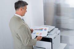 Uomo d'affari Looking At Paper con i grafici dalla stampante a colori fotografie stock