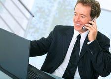 Uomo d'affari maggiore attivo sul telefono in ufficio Fotografie Stock Libere da Diritti