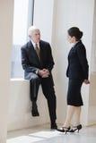 Uomo d'affari maggiore che comunica con il collega della donna. Immagine Stock