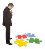 Uomo d'affari maggiore che monta un puzzle di puzzle Immagine Stock