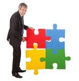 Uomo d'affari maggiore che monta un puzzle di puzzle Fotografie Stock Libere da Diritti