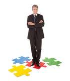 Uomo d'affari maggiore che si leva in piedi su un puzzle di puzzle Fotografia Stock Libera da Diritti