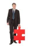 Uomo d'affari maggiore che tiene un puzzle di puzzle Immagine Stock Libera da Diritti