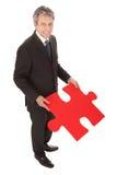 Uomo d'affari maggiore che tiene un puzzle di puzzle Immagini Stock