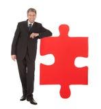Uomo d'affari maggiore che tiene un puzzle di puzzle Fotografia Stock