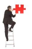 Uomo d'affari maggiore che tiene un puzzle di puzzle Immagini Stock Libere da Diritti