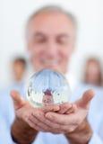 Uomo d'affari maggiore che tiene una sfera di cristallo fotografia stock