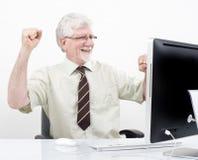 Uomo d'affari maggiore che vince davanti al calcolatore fotografia stock